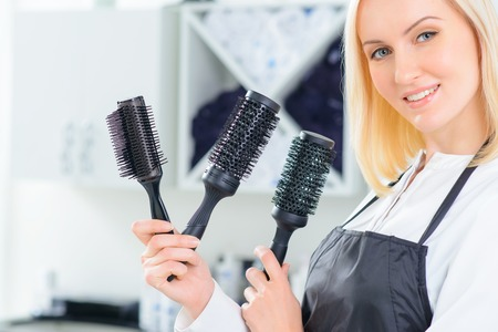 stylists: Stylists tools. Young female hair stylist demonstrating various hairbrushes. Stock Photo