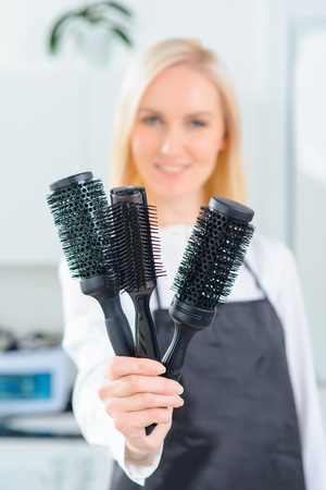 hairstylists: Special hairbrushes. Young female hair stylist demonstrating various hairbrushes. Stock Photo