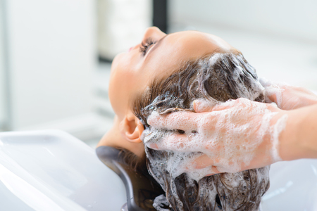 hairstylists: Washing procedure. Client is resting while its hair is being washed. Stock Photo