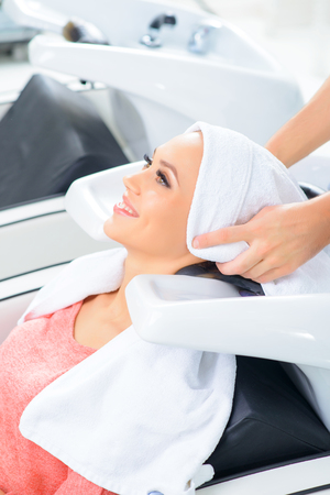 hairstylists: End of procedure. Smiling client waits while her hair is being dried off with towel.