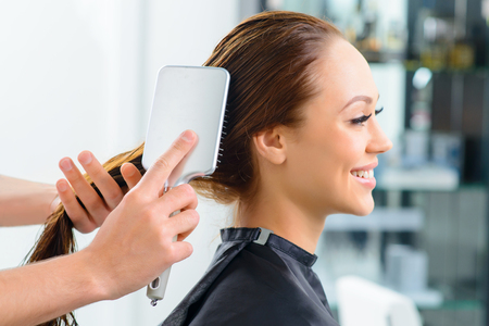 hairstylists: Hair brushing. Young appealing client is smiling while her hair is being brushed by a professional.