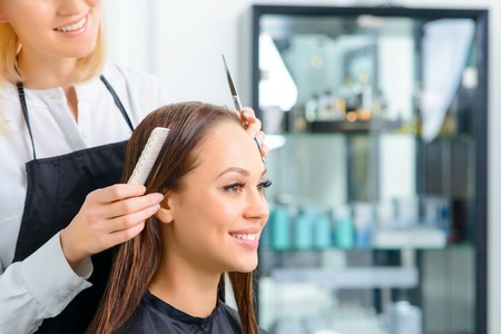 hairstylists: Pre-trimming process. Stylist is doing final moves before starting to trim clients hair. Stock Photo