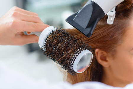 hairstylists: Hairdryer in use. Close up of hair styling process by using hairdryer and round brush. Stock Photo
