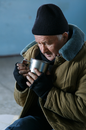 joblessness: Beggar and cup. Sad old-aged homeless man is sitting on the floor and drinking something from his iron cup.