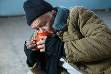 desperately: Thirsty beggar. Upset homeless man is lying on concrete color and desperately drinking water from the cup. Stock Photo