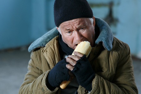 Hungry man. Upset old-aged homeless man is biting at piece of bread.