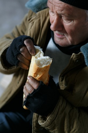 joblessness: Hungry homeless. Distressed senior homeless man eating bread in deserted building. Stock Photo