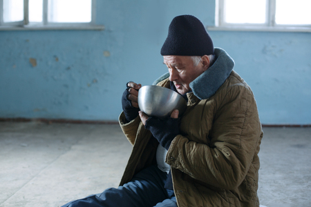 beggars: Beggars meal. Senior-aged beggar looks sad while eating from his old iron bowl. Stock Photo
