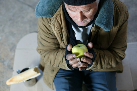 vagrant: Homeless with apple. Old vagrant man is sitting on cardboard and holding single green apple.
