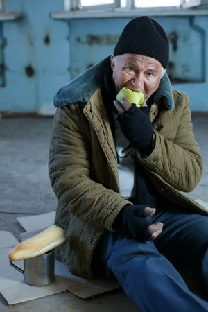 vagabond: Eating apple. Old-aged vagabond is sitting on cardboard and hungrily eating an apple.