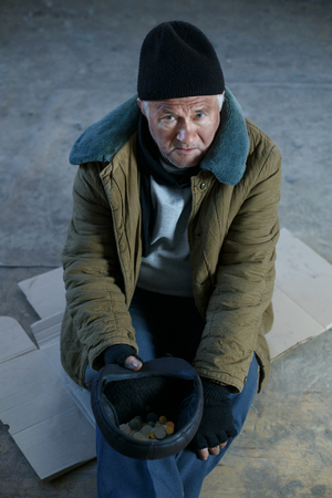 beggar: Asking for help. Depressed old beggar is sitting on cardboard and holding his cap to ask for money. Stock Photo