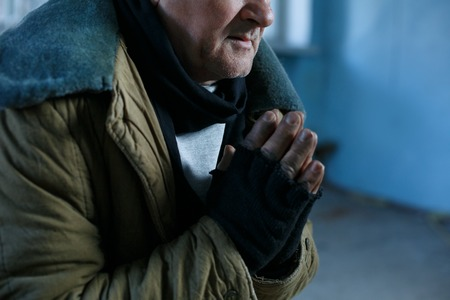 destitute: Desperate man. Old-aged beggar is sitting and holding his hands in praying gesture. Stock Photo