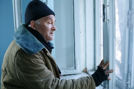 Unhappy man. Old-aged beggar is sadly looking out of the window in deserted building. Stock Photo