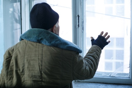 joblessness: Unhappy man. Old-aged beggar is sadly looking out of the window in deserted building. Stock Photo