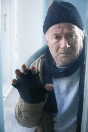 joblessness: Scared and unhappy. Old-aged beggar looks scared and desperate while looking out of the window. Stock Photo