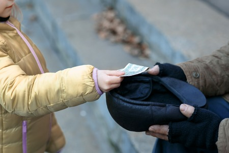 homeless person: Getting help. Somebody gives money to a homeless person. Stock Photo