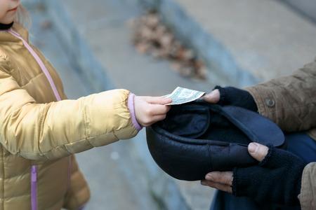 vagabundos: Obteniendo ayuda. Alguien da dinero a una persona sin hogar.