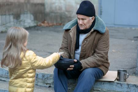 vagabundos: Obteniendo ayuda. Kind niña le da dinero a una persona sin hogar. Foto de archivo