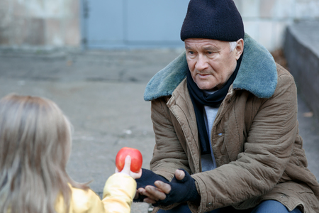 Getting food. Kind little girl gives apple to a homeless person.