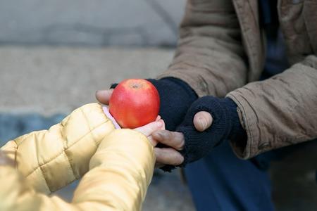 pobreza: La obtención de alimentos. Tipo pequeño niño da la manzana a una persona sin hogar.