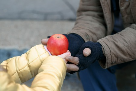 Getting food. Kind little child gives apple to a homeless person.