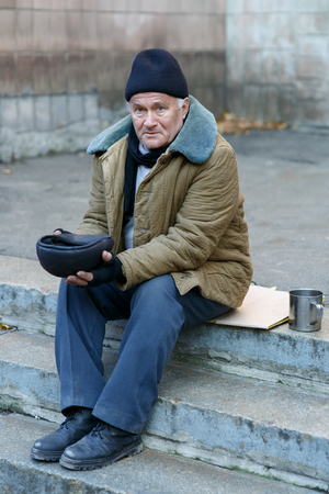 beggar: Beggar and cap. Sorrowed old-aged homeless man sitting outside and holding his tip cap.