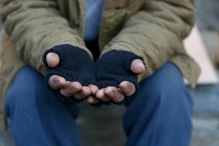vagabundos: Hombre en necesidad. Hombre sin hogar infeliz es la celebraci�n de las manos para obtener ayuda. Foto de archivo
