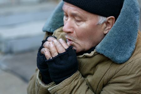 to get warm: Freezing outside. Senior-aged beggar is sitting outside and breathing onto his hands to get warm.