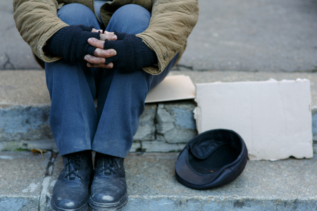 beggar: Asking for help. Depressed old beggar is sitting outside and waiting to get some help. Stock Photo