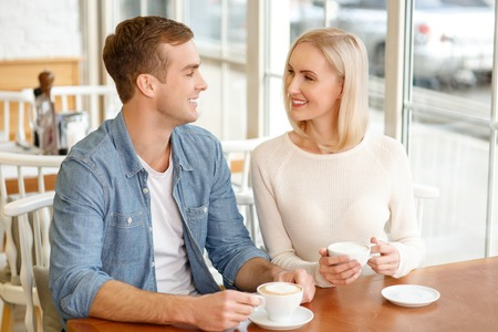 caf: Brisk conversation. Cheerful content smiling couple sitting at the table and drinking coffee together while talking Stock Photo