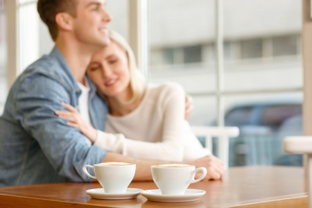 caf: Love me tender. Selective focus of cups of coffee standing on the table with pleasant loving couple embracing in the background