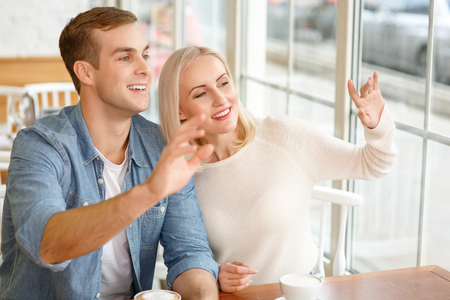 caf: Hello. Pleasant smiling jubilant couple sitting at the table in the cafe and drinking coffee while welcoming someone