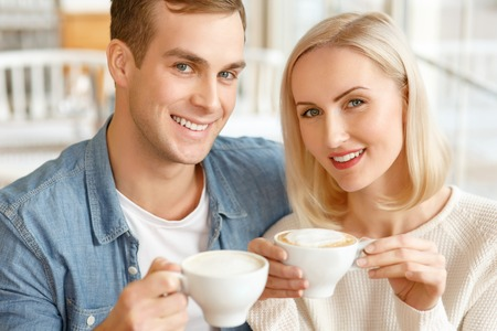 caf: Full of joy. Pleasant content smiling couple sitting in the cafe and drinking coffee while feeling glad