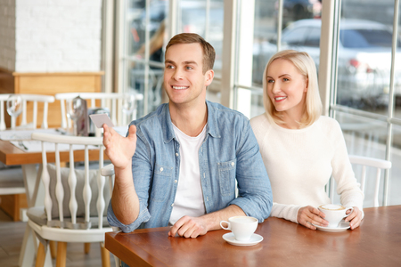 caf: may we have the bill. Pleasant smiling vivacious couple sitting in the cafe and drinking coffee while waiting for a waiter