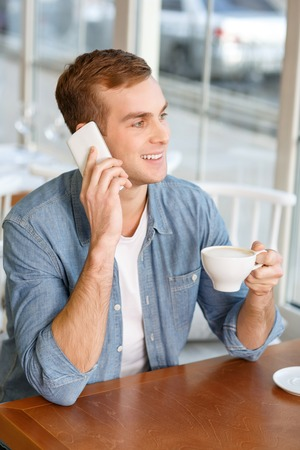 caf: Life is great. Happy smiling handsome man drinking coffee and talking on mobile phone while resting in the cafe