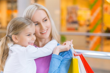 pleasant: Pleasant time. Close up of pleasant smiling woman holding her daughter on hands while having shopping together