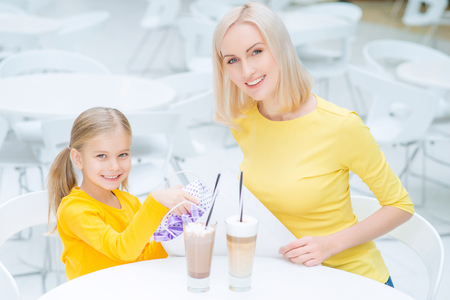 caf: Nice day. Content smiling  mother and daughter sitting at the table and drinking coffee while resting in the cafe