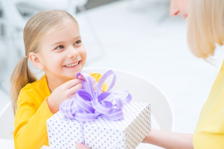 caf: In a good mood. Close up of cheerful cute little girl holding box with surprise and giving it to her mother while resting in the cafe