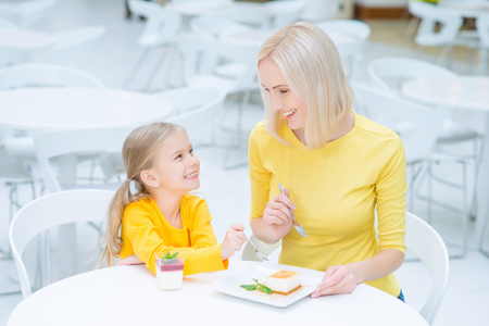 beautiful mother: Get inspiration. Pleasant jubilant mother and daughter sitting at the table and eating desserts while resting in the cafe Stock Photo