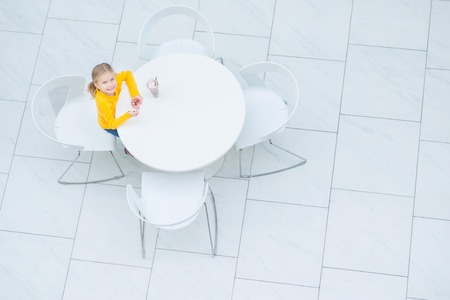 caf: Sweet memories. Top view of little girl sitting at the table and eating dessert while resting in the cafe Stock Photo