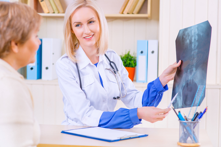all right: Everything is all right. Professional upbeat nurse sitting at the table and showing x ray photo to her patient Stock Photo