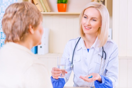 medical exam: Best medicines. Pleasant smiling  positive nurse holding pill and glass of water in her hands while giving to her patient and sitting at the table Stock Photo
