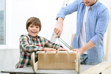 spending full: Full of happiness. Cheerful little boy and his father standing near table and constructing from wood while spending time together Stock Photo