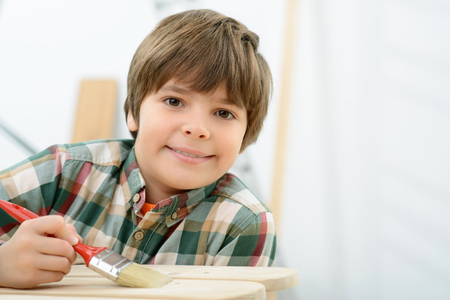 feeling happy: Be creative. Close up of pleasant smiling content little boy holding brush and painting sled while feeling  happy
