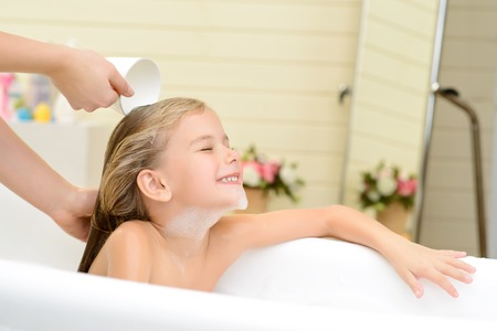 woman bath: Like this moment. Pleasant cute little girl sitting in the bath tube and closing her eyes while her mother washing her hair