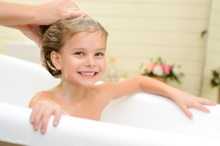 woman in bath: Full of delight. Pleasant little girl sitting in the bath tube and smiling while her mother washing her hair Stock Photo