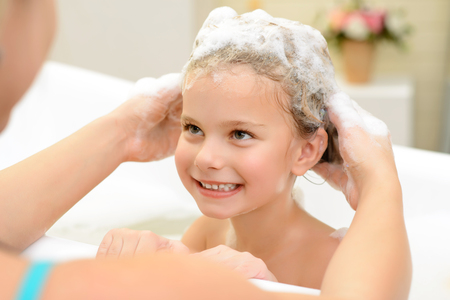 woman in bath: Love you so  much. Pleasant little girl sitting in the bath tube while her mother washing her hair