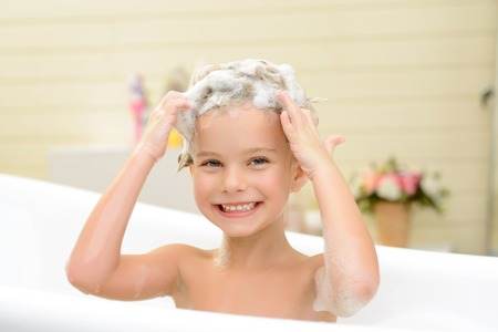 woman in bath: On the edge of delight. Pleasant smiling little girl sitting in the bath tube and washing her hair while feeling glad