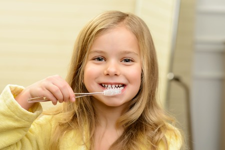 brush teeth: Take care of your health. Portrait of cute smiling girl holding tooth brush and cleaning her teeth while feeling glad Stock Photo