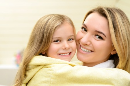 pretty face: Best friends. Close up of pleasant beautiful loving mother and her little daughter embracing and smiling while evincing love